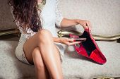 stock photo of mystique  - legs and torso of model girl sitting on victorian sofa looking through red purse - JPG