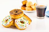 picture of donut  - traditional donuts of chocolate and vanilla in front slightly out of focus and another plate of covered donuts in background next to coffee cup - JPG