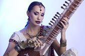 stock photo of sari  - Beautiful Young Indian Woman in Traditional Sari Clothing with oriental jewelry Bridal Makeup Playing the Sitar - JPG