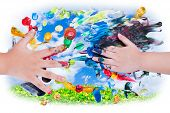 image of finger-painting  - Closeup of little children hands doing finger painting with various colors on sky and green clover background - JPG
