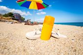 foto of suntanning  - Closeup photo of yellow suntan lotion and flip flops lying on sandy beach