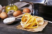 stock photo of pasta  - Preparing pasta by pasta machine on rustic wooden background - JPG