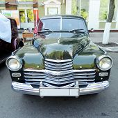 picture of 1950s  - Forebody of executive retro car of 1950s with radiator bumper headlights on the city street - JPG