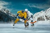 picture of ice hockey goal  - Ice hockey player in action outdoor around mountains - JPG