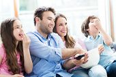 image of popcorn  - Family watching TV and eating popcorn - JPG