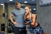 sport, training, fitness, lifestyle and people concept - young woman with personal trainer flexing b poster