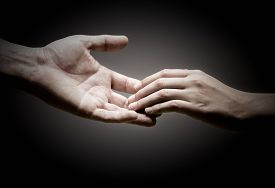 picture of empathy  - two hands are touching each other over black background concept of solidarity or empathy - JPG
