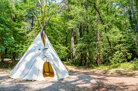 picture of tipi  - A Native American teepee in a wooded clearing - JPG