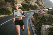Female Athlete Running Outdoors On Highway poster