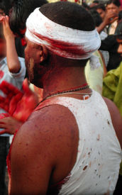 stock photo of muharram  - a shiite man after bleeding himself beeting his chest with blood soaked hands mourning Imam Hussain  - JPG