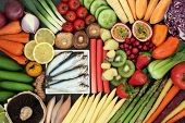 Super food for a healthy diet concept with fresh sardines, vegetables and fruit forming an abstract  poster
