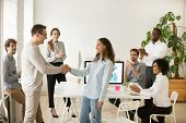 Boss Shaking Hand Of Young Shy Woman Congratulating Successful Employee With Promotion, Hiring Inter poster