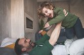 Portrait Of Happy Father Fooling Around With Glad Child On Cozy Bed In Room poster