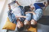 Top View Portrait Of Happy Kids And Cheerful Father Looking At Electronic Tablet While Lying On Bed. poster