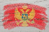 Flag Of Montenegro On Grunge Wooden Texture Painted With Chalk