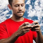 young man typing on mobile phone against a blue sky background