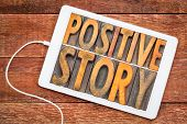 positive story - word abstract in vintage letterpress wood type on a digital tablet against rustic w poster
