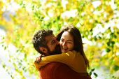 Man And Woman With Happy Faces On Autumn Trees Background. Couple In Love Cuddles And Play In Park.  poster