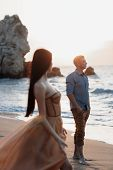 Couple In Love At Dawn By The Sea. Honeymoon Trip. Man And Woman Traveling. Happy Couple By The Sea  poster