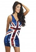 Beautiful young woman wearing British flag union jack flag dress. Image isolated against white.