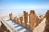 Ruins of ancient fortress Masada. Dead Sea is at background. Masada is the name for ancient palaces and fortifications in the South District of Israel on top of an isolated rock plateau. Israel