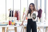 Portrait of young adult fashion designer hold EDC Machine ready for customer to make a payment with  poster