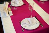 Restaurant Table Setout With White Plates, Silverware And Magenta Decoration poster