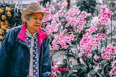 Old Elder Woman Resting In Garden. Asian Elderly Female Relaxing Outdoors. Senior Leisure Lifestyle poster