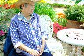 Old Elder Woman Resting In Garden. Elderly Female Relaxing Outdoors. Senior Leisure Lifestyle poster