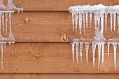 Icicles hang from a wood cabin in on a chilly winter day