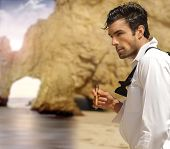 stock photo of bachelor party  - Sexy masculine man in formal clothes smoking cigar on exotic beach - JPG