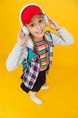 Cute Hipster Teenager Listening Music Headphones Yellow Background. Cool Schoolgirl. Teens Fashion.  poster