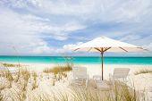 Two chairs under umbrella on stunning Caribbean beach