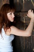 picture of red hair  - Strong fierce young women standing against the old doorway - JPG