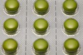 Green tablets in blister pack arranged with beautiful pattern. Global healthcare concept. Antibiotic poster