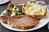 stock photo of baked potato  - A grilled rib steak with baked potato and salad - JPG