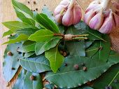 Bay Leaf Or Laurel (laurus Nobilis), Sliced Garlic & Garlic Clove On Wooden Background. Organic Fres poster