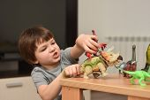 Child Play With A Dinosaur Toys. Boy Having Fun Playing With A Toy Dinosaur, Little Paleontologist poster
