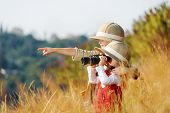 pic of safari hat  - Happy young safari adventure children playing outdoors in the grass with binoculars and exploring together as brother and sister - JPG