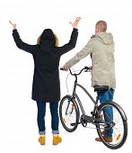 Back view of couple in winter jacket. man on a bicycle and a woman. Rear view people collection. bac poster