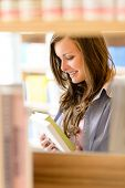 Young student woman reading book among library shelves