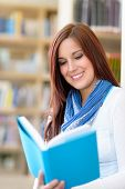 Female high school student at library reading book