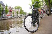 AMSTERDAM, HOLLAND - MAY 29: Detail of bicycle chained by canal in the city centre. May 29, 2012 in
