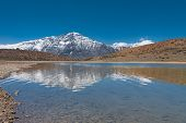 foto of himachal  - A pristine clear alpine lake reflects a beautiful snowcapped mountain in the himalayas near the town of Dhankar Himachal Pradesh India - JPG