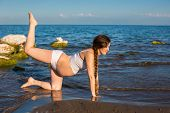 Pregnant Woman In Sports Bra Doing Exercise In Relaxation On Yoga Pose On Sea.  The Concept Of Healt