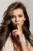 picture of hush  - Portrait of a beautiful woman with healthy long brown hair and fresh makeup making a hush gesture - JPG