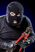 picture of wire cutter  - a burglar wearing a balaclava holding huge wire cutters over black background - JPG