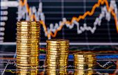 stock photo of golden coin  - Down trend stacks of golden coins and financial chart as the background - JPG