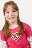 Young Caucasian girl in a heart pattern shirt and smiling