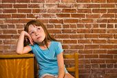 Young girl leaning on school desk thinking